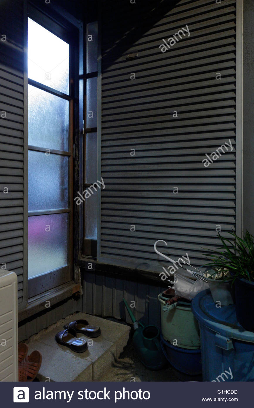 from inside lighted up door of a residential house with slippers in front Japan - Stock Image