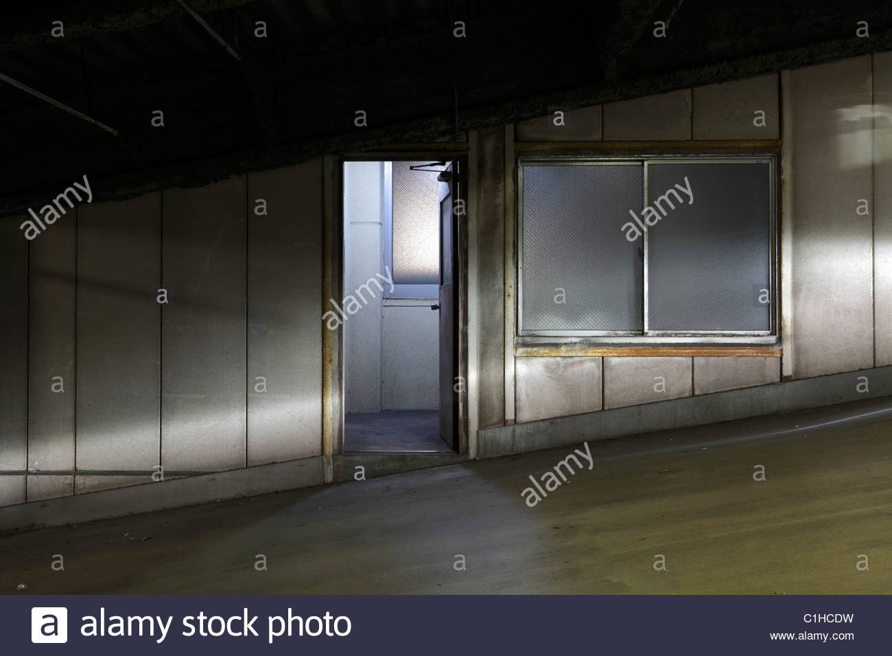 pedestrian door in a parking garage with head lights from a car - Stock Image