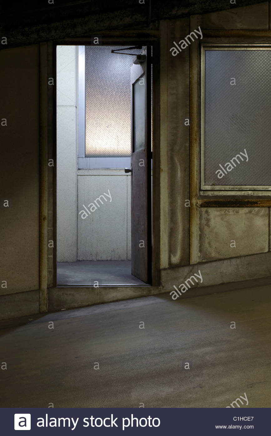 pedestrian door in a parking garage with light coming from the hall - Stock Image