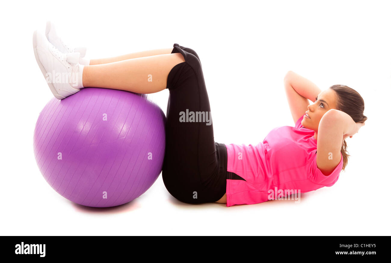 A young woman doing an abdominal crunch using a purple exercise ball - Stock Image