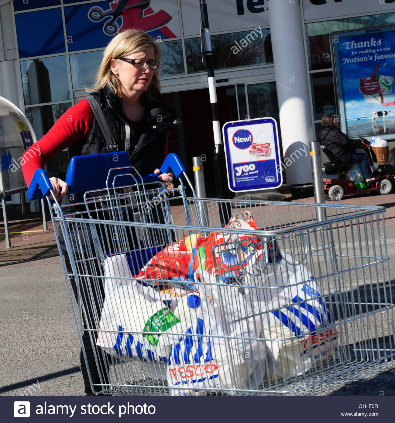 Woman pushing a shopping trolley full of Tesco's carrier bags, UK. Front view adult woman with Tesco shopping - Stock Image