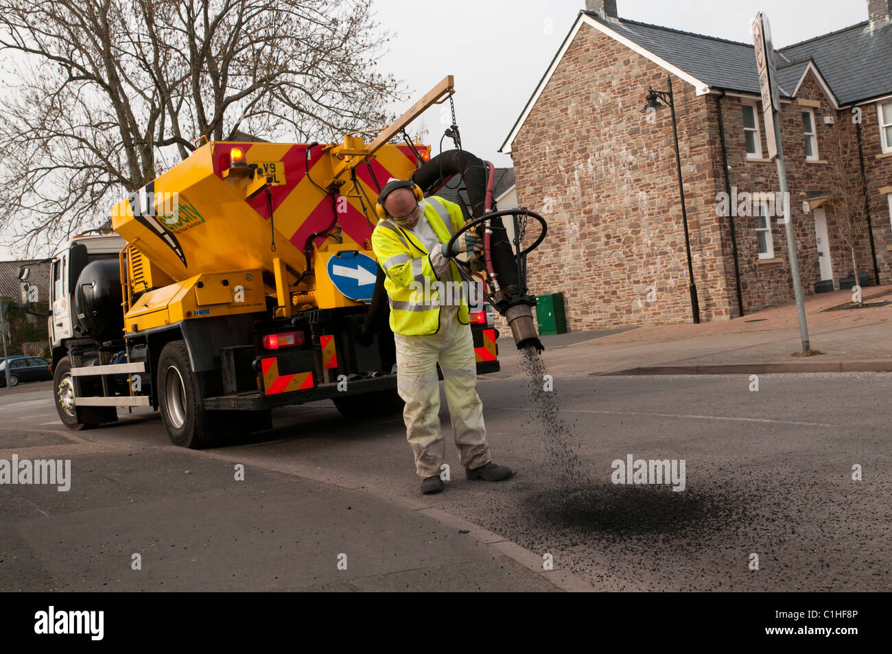 A VELOCITY worker repairing potholes in a road with a high pressure spray blaster system, UK - Stock Image
