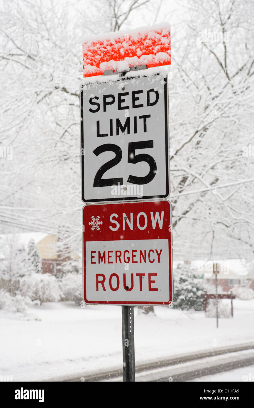 A snow emergency route and speed limit sign seen during a heavy snowfall, Maryland, USA. - Stock Image