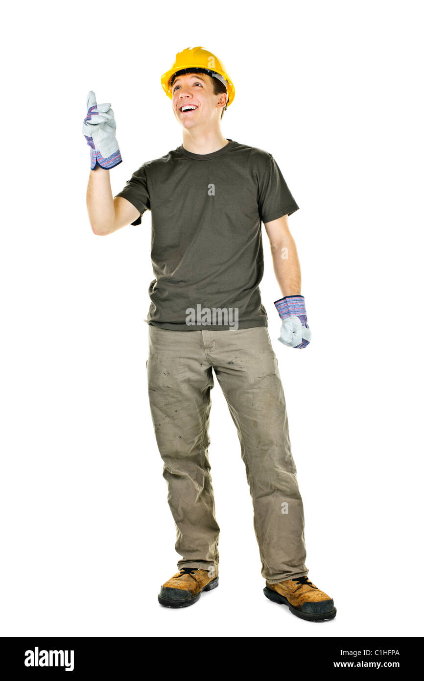 Smiling construction worker pointing up standing isolated on white background - Stock Image