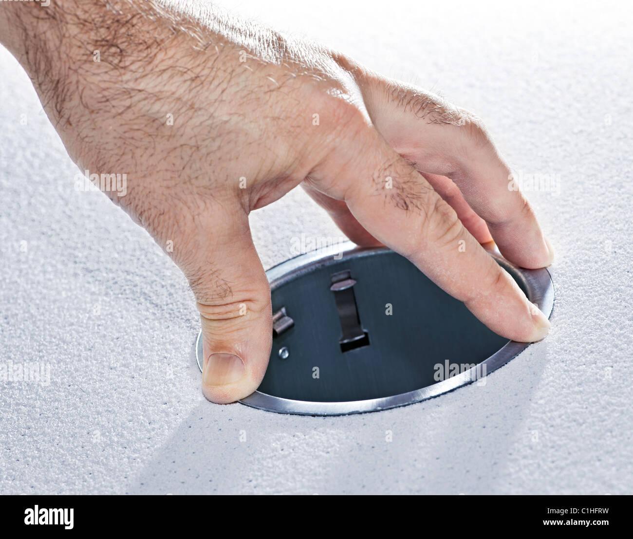 Hands Installing Round Metal Pot Light Fixture Into Ceiling Tile