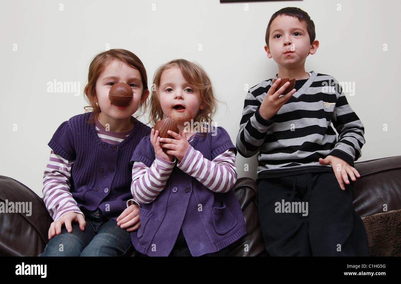 Children eating chocolate Easter Eggs, UK - Stock Image
