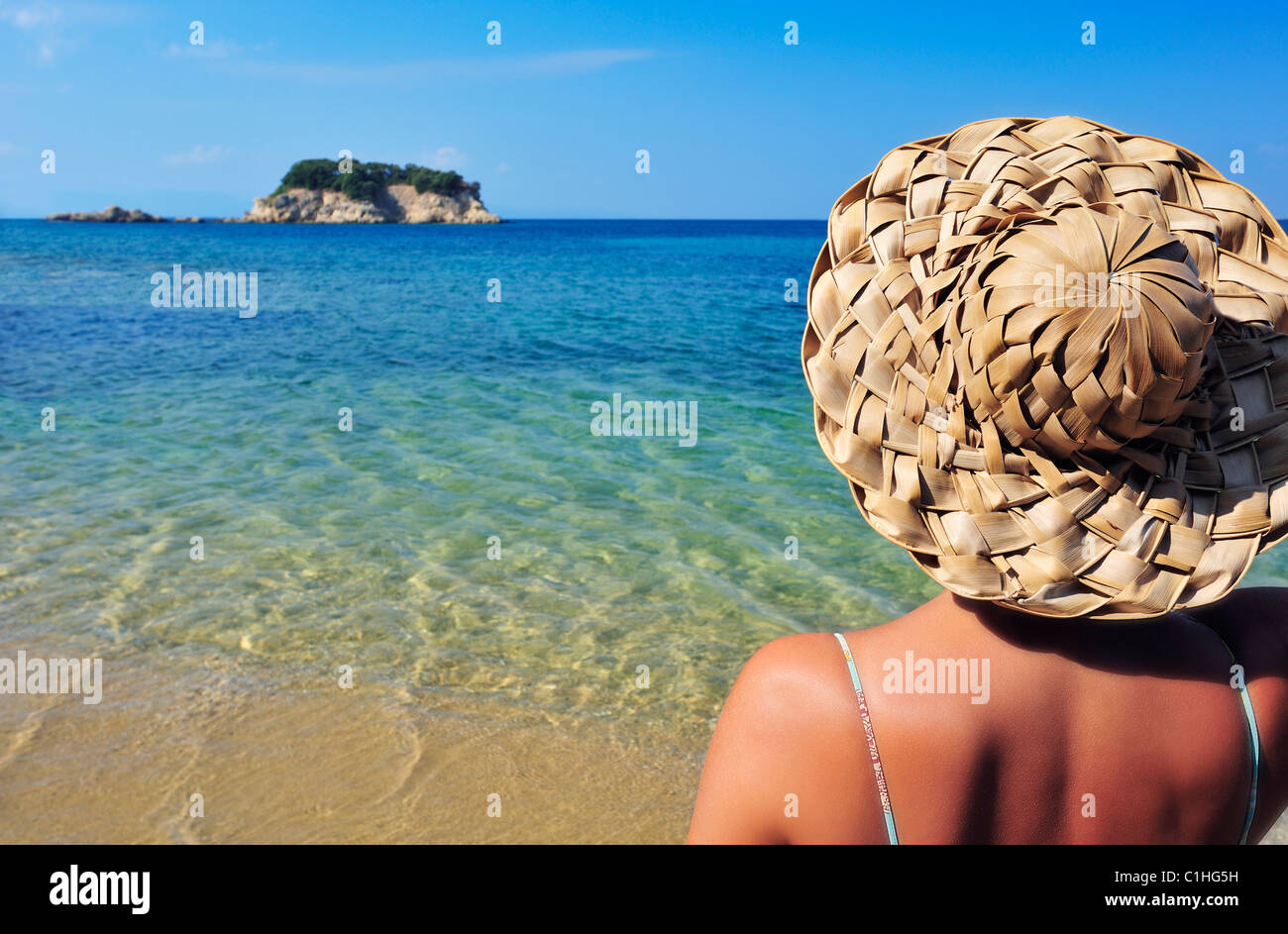 Closeup image of a young woman in a straw hat and bikini, looking at a tiny island in the Mediterranean - Stock Image