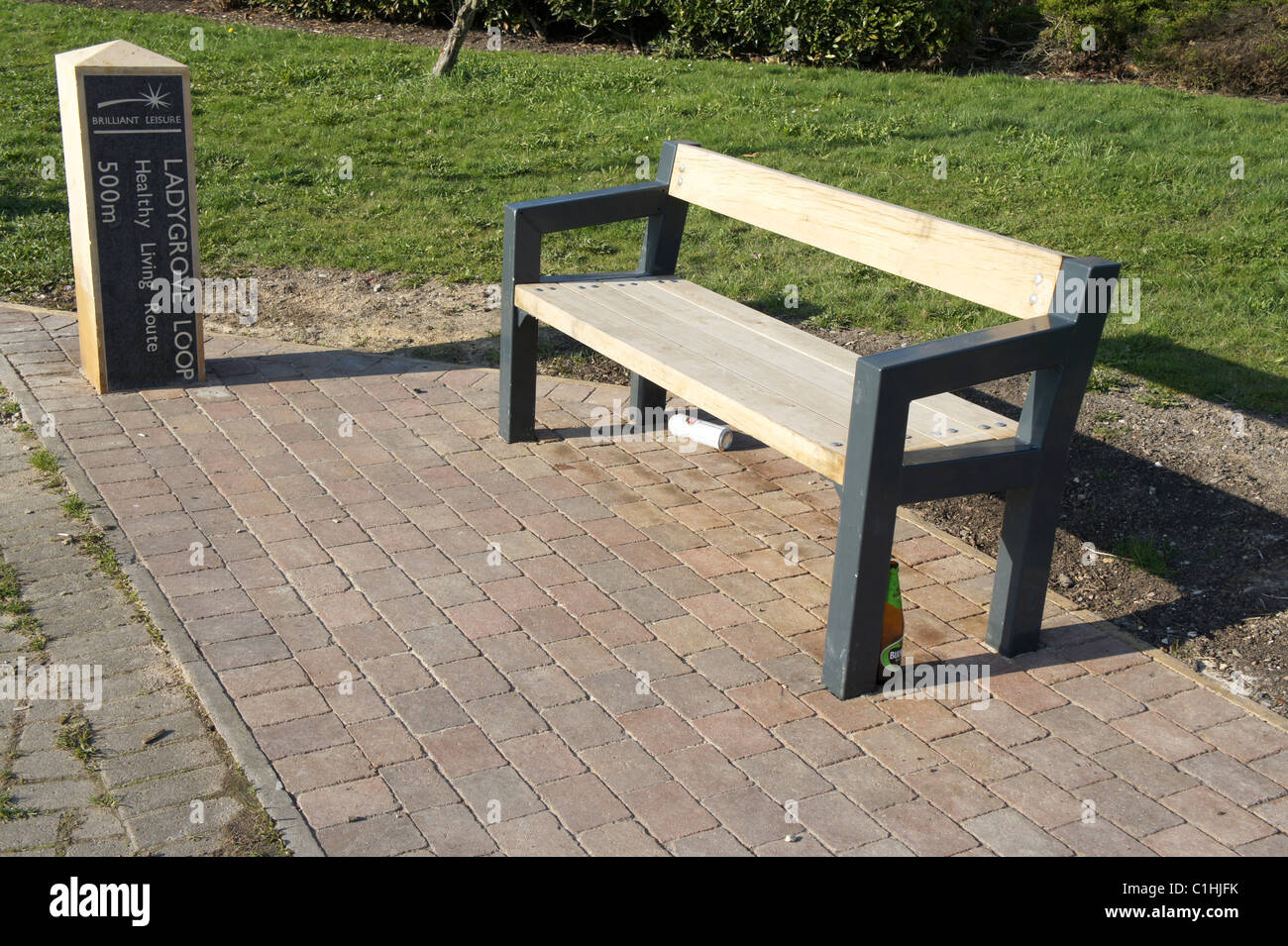 Ladygrove Loop, Didcot, Oxfordshire, healthy Living Route, Park bench with beer bottle and can. Anti Social behavior. - Stock Image
