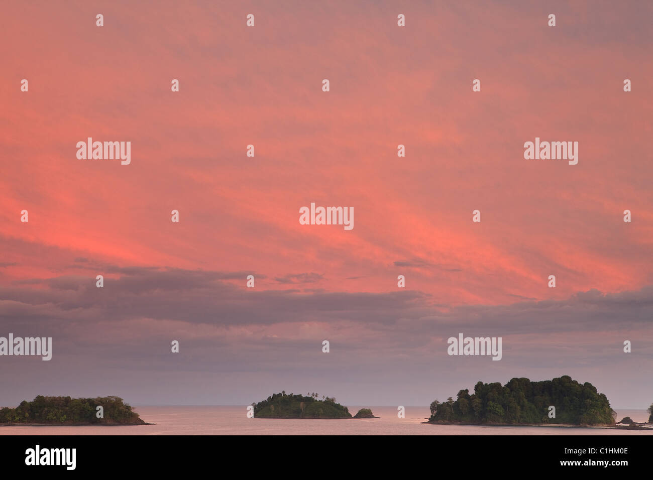 Colorful skies at dusk over small islands seen from the northeast side of Isla Coiba, Pacific ocean, Veraguas province, Stock Photo