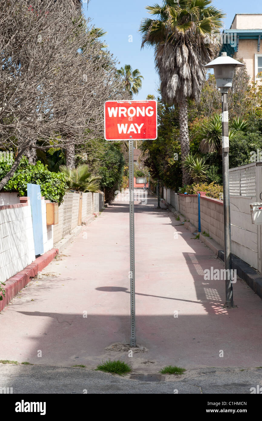 A wrong way sign in front of an alleyway to fend off traffic from driving through. - Stock Image