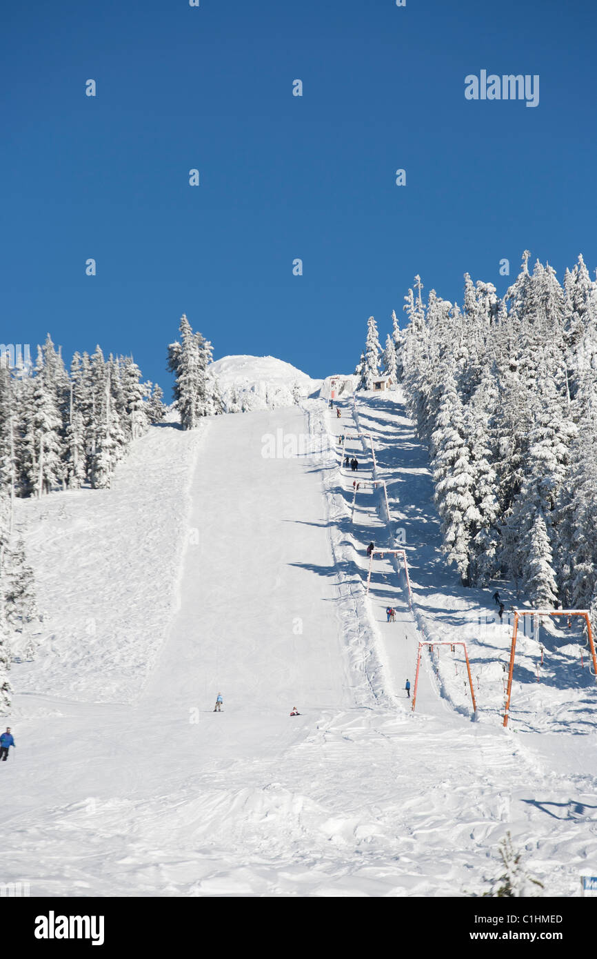 People riding the t-bar at Mt.Cain ski resort. - Stock Image
