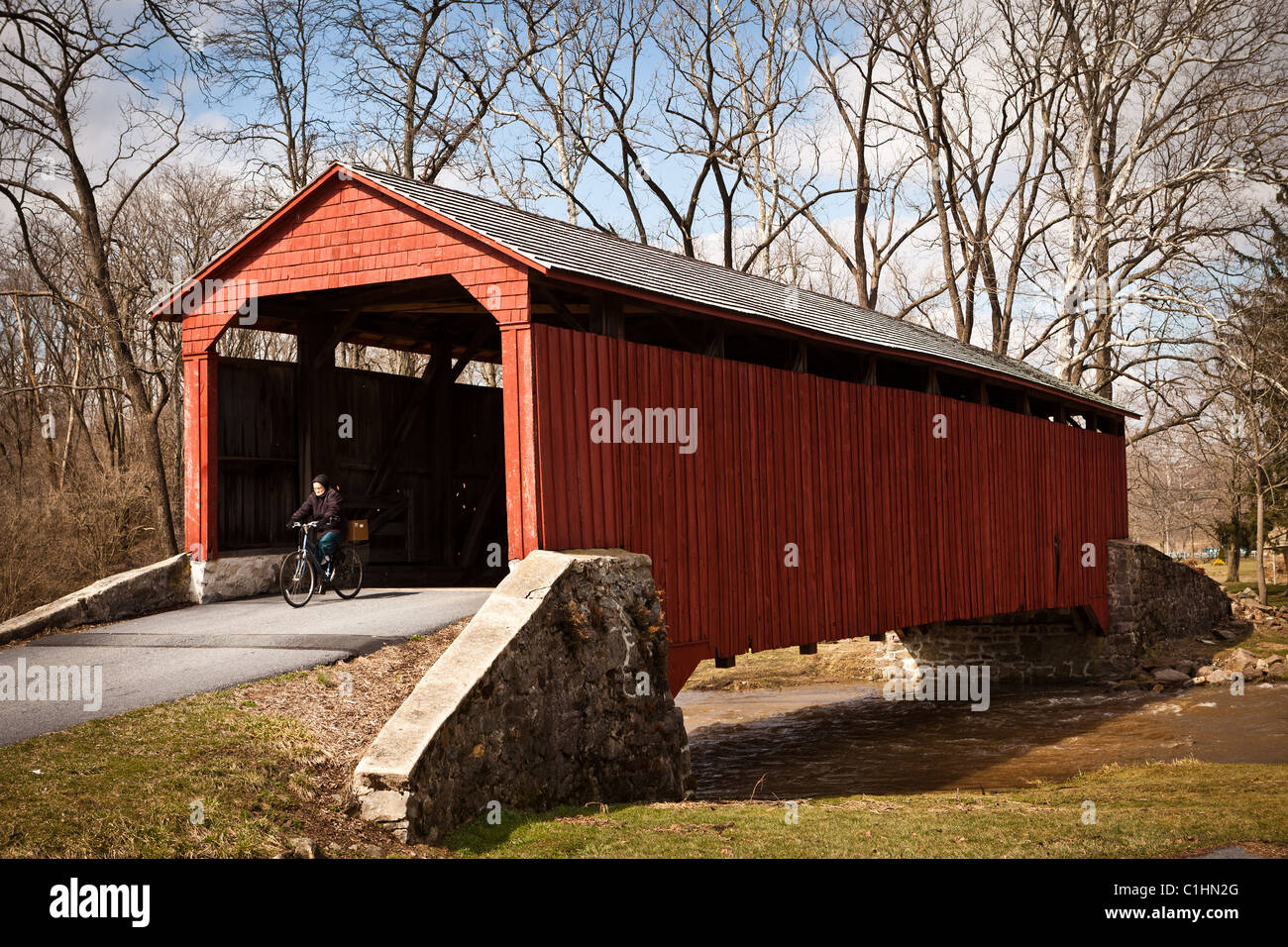 Amish women rides her bike through Pool Forge Covered Bridge Caernarvon Township, PA - Stock Image