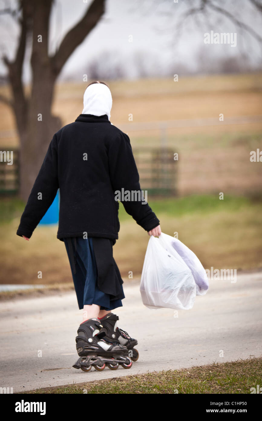 Amish girl roller blades home from school in Gordonville, PA. Stock Photo