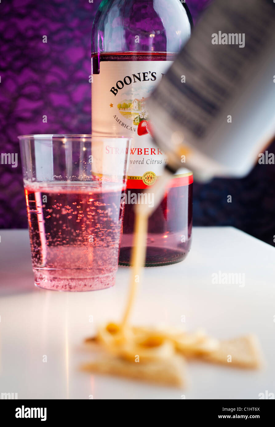Cheap wine and canned spray cheese. - Stock Image