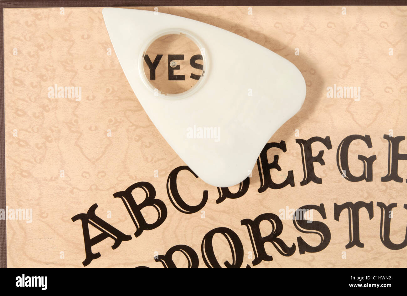Ouija board with the planchette pointing to YES. This is the vintage Ouija board and classic arrangement of the - Stock Image