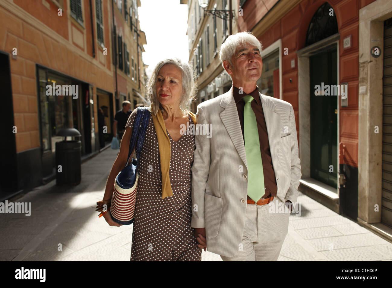 Senior couple strolling through town, Italy - Stock Image