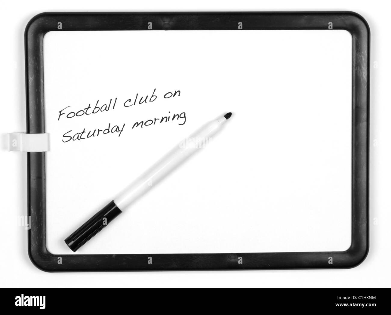 White message board and black marker pen with the message 'Football club on Saturday morning' - white background. - Stock Image