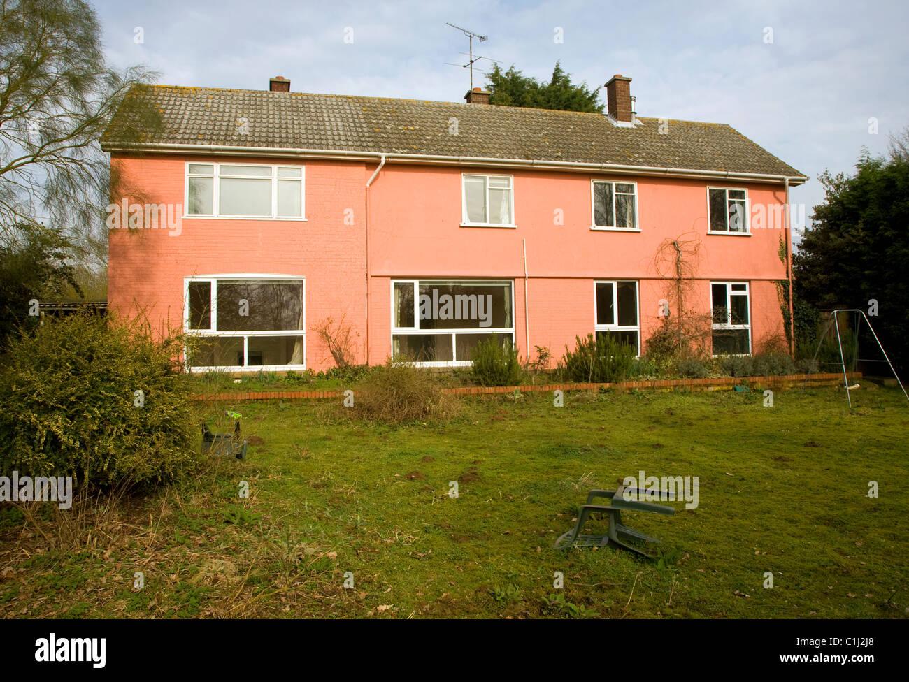 Orange washed empty large detached house abandoned Stock Photo
