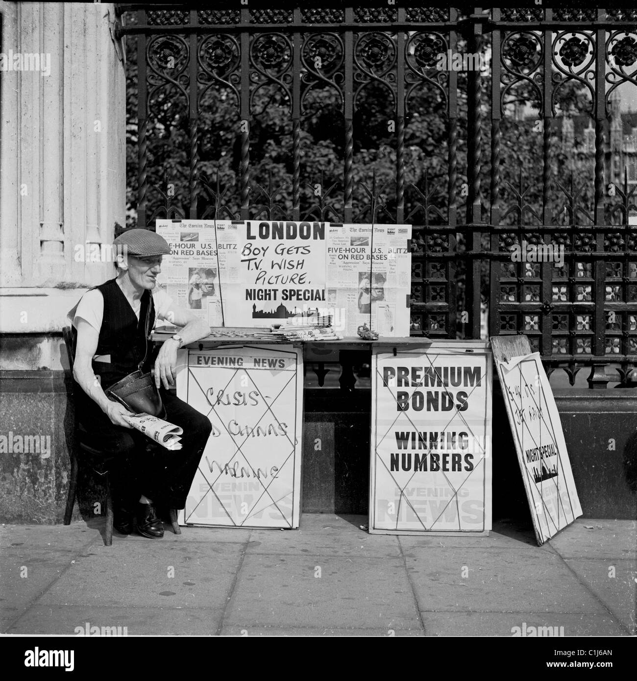 1950s, London, Elderly man in flat cap and holding a newspaper, sitting on a small chair on the pavement, selling - Stock Image