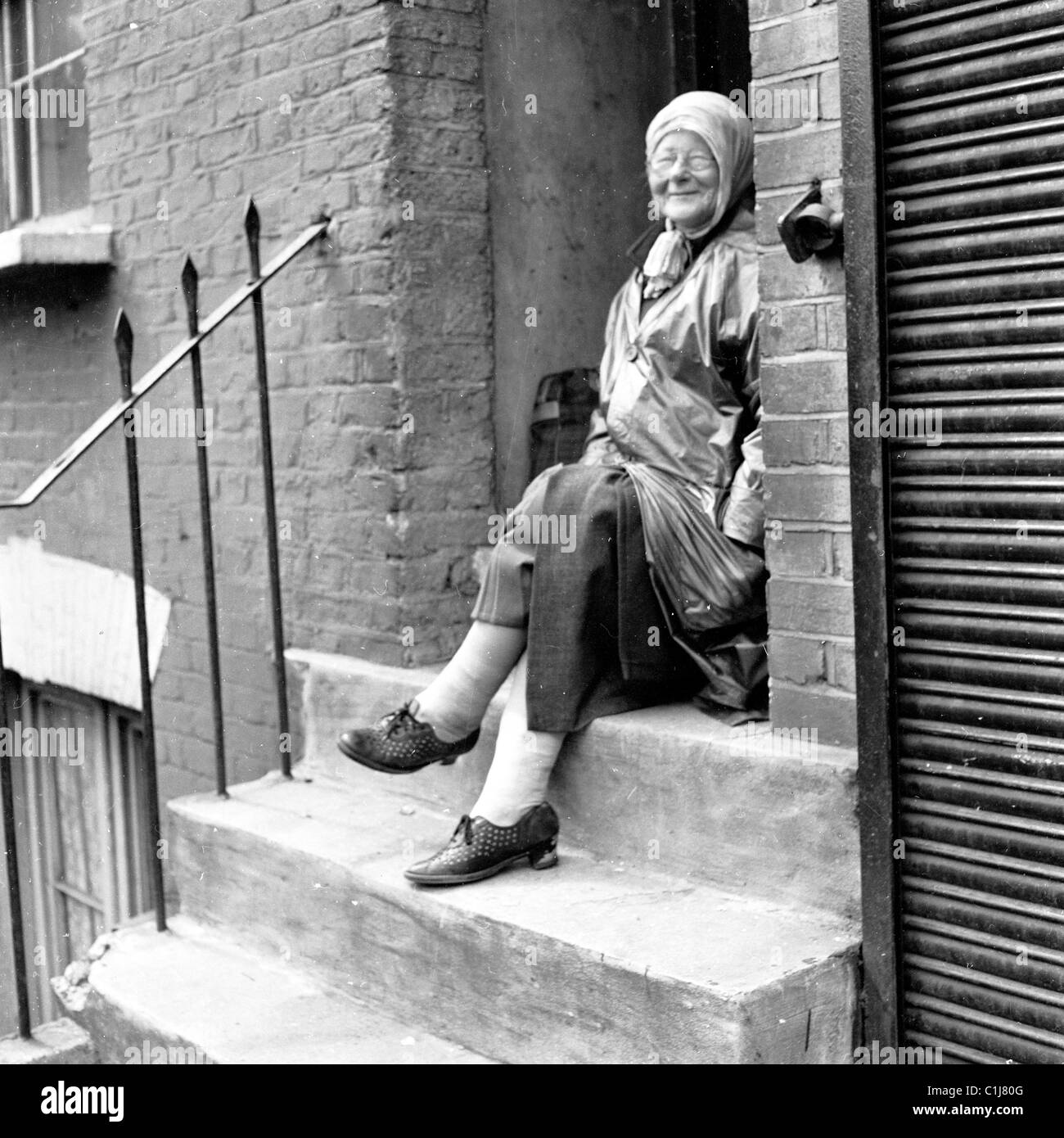 1960s, London, an elderly lady with head scarf wearing a raincoat or mac sitting on a stone step of a victorian Stock Photo