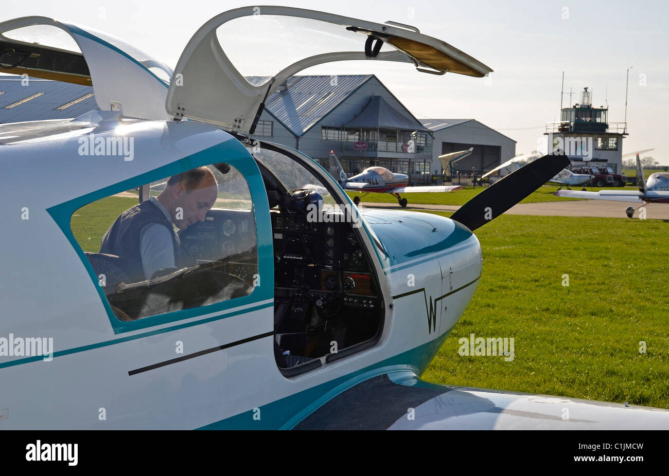 private pilot preparing light aircraft at sywell airfield - Stock Image
