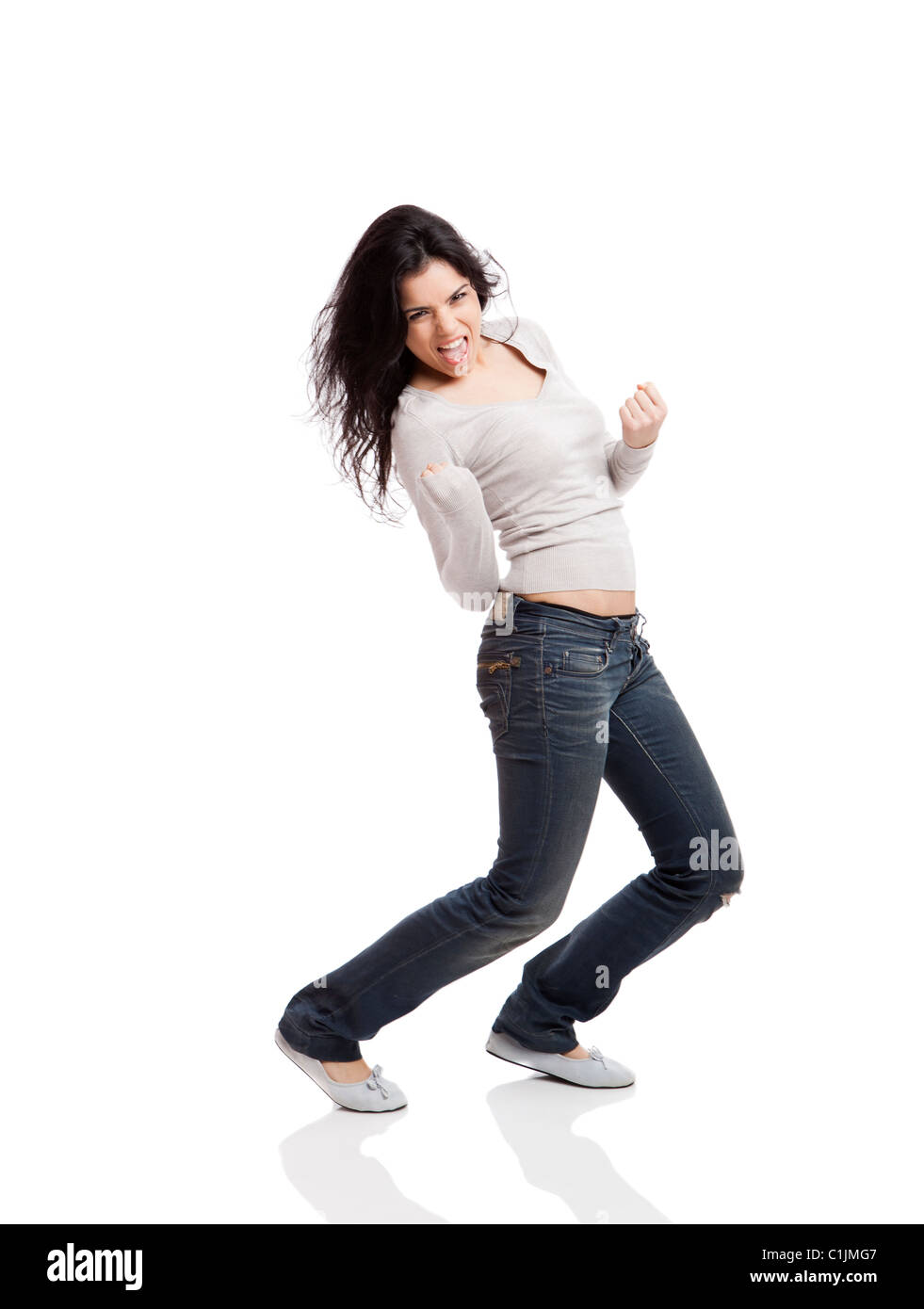 Happy young woman with arms up after wining something, isolated against a white background - Stock Image
