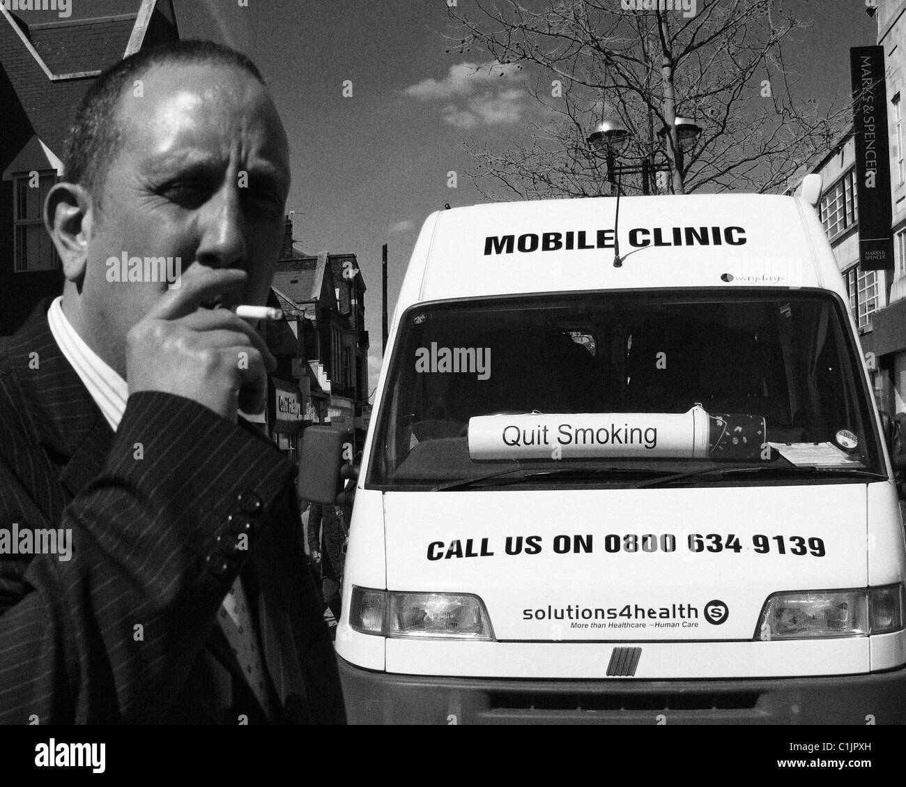 A smoker by a mobile clinic - Stock Image