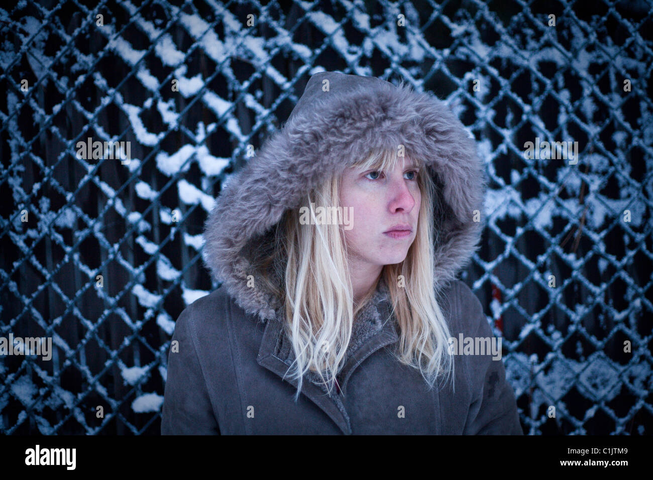 girl against fence in snow looking mad - Stock Image