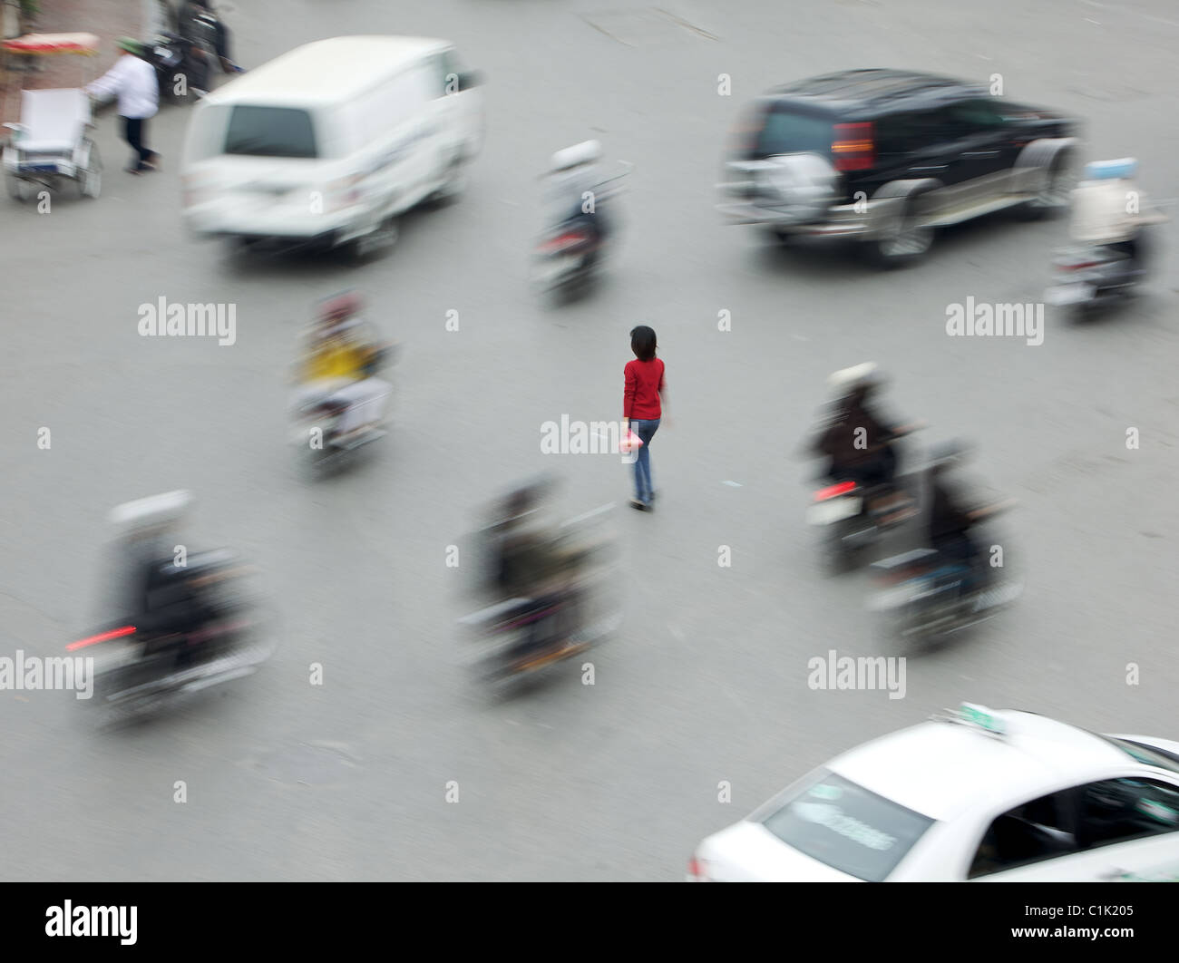 A lone woman crosses a busy road junction in the heart of Hanoi, Vietnam (this is not photo-shopped) - Stock Image