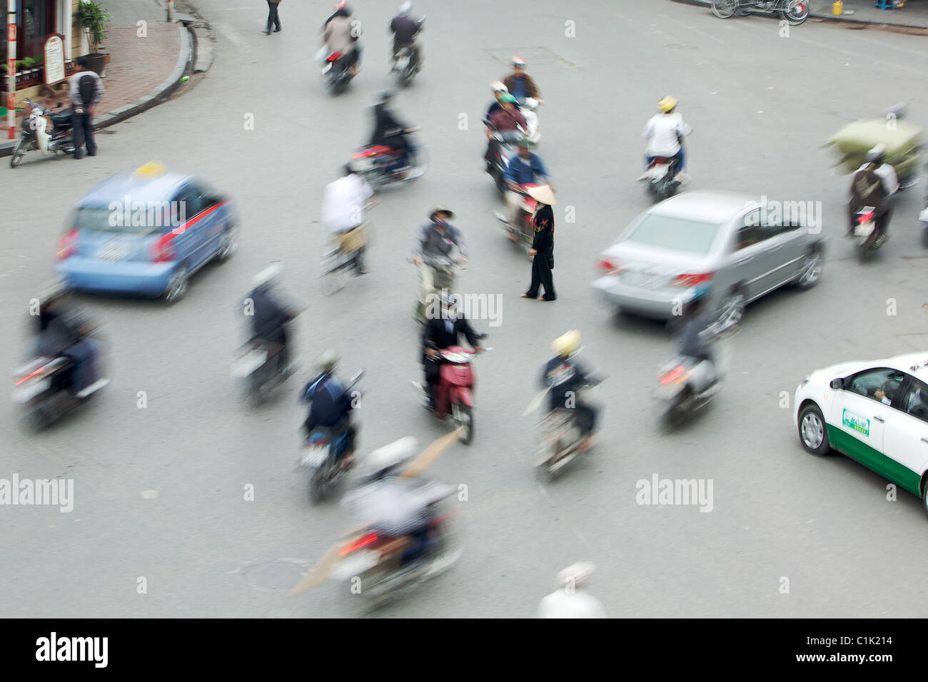 A lone woman is surrounded by motorbikes on a busy street in Hanoi, Vietnam (this has not been photo-shopped!) - Stock Image