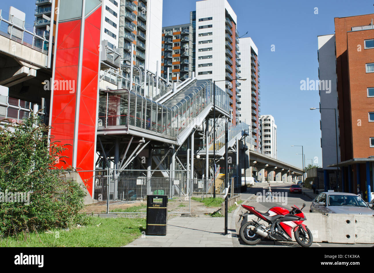 East India Dock DLR station station Poplar E14, London. Apartment blocks behind Uk Red motor bike in foreground - Stock Image
