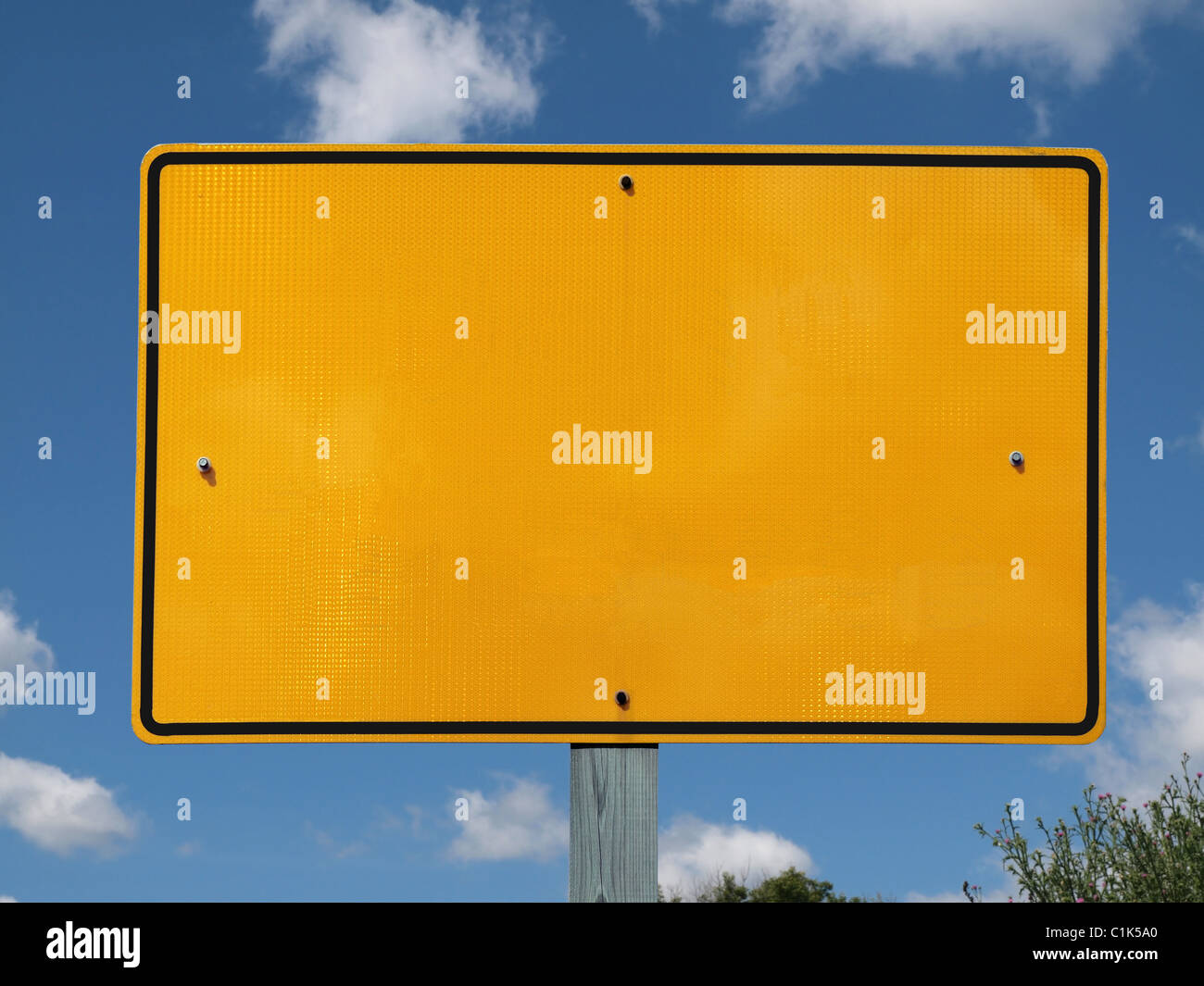 Blank reflective yellow highway message sign with puffy clouds. Stock Photo