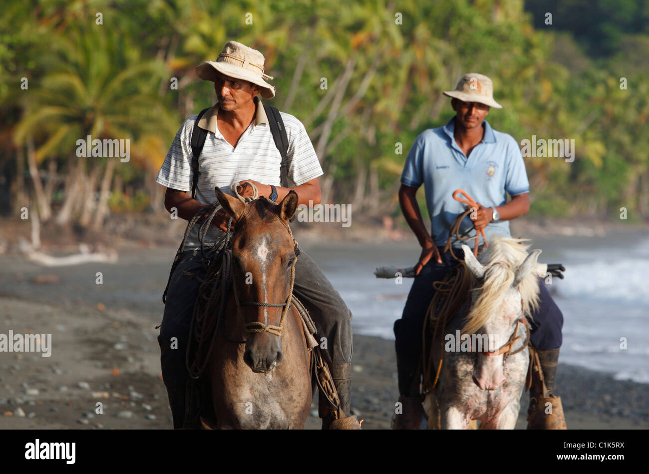 Costa Rican men ride horses on the beach in Punta Banco, Costa Rica - Stock Image