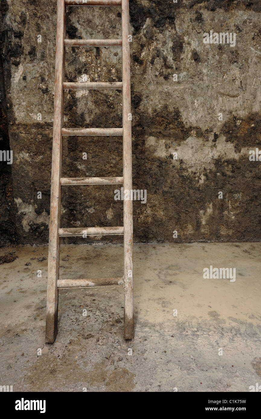 Ladder in a muddy hole - Stock Image