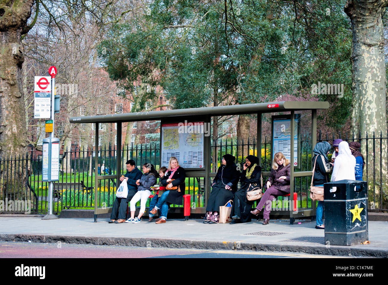 Group of people waiting at a Bus Shelter in Bethnal Green, London. - Stock Image