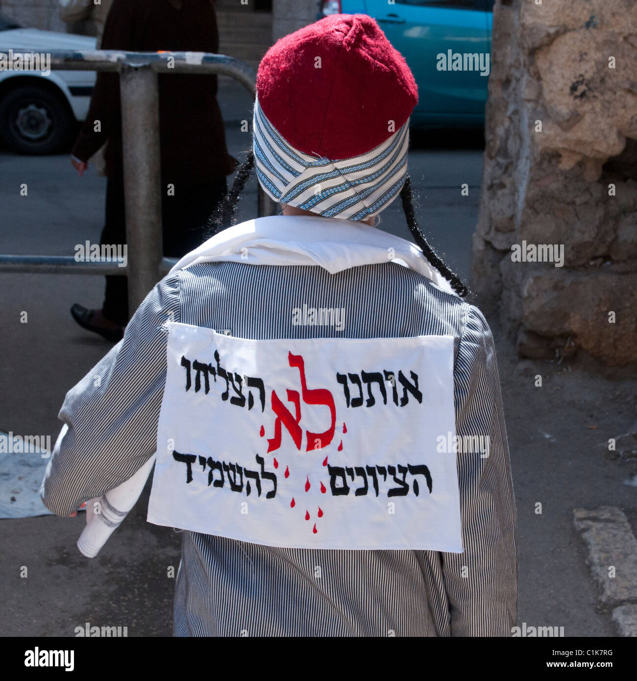 Purim Jewish festival.Child wearing a traditional Yemenite costume with sign: the sionists have not succeded in - Stock Image