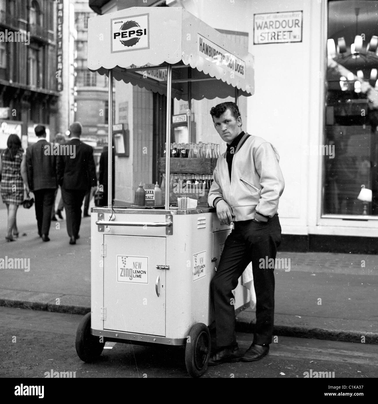 196s, London. Portable hot dog stand ans seller on the corner of Wardour Street, in this historical picture by J - Stock Image