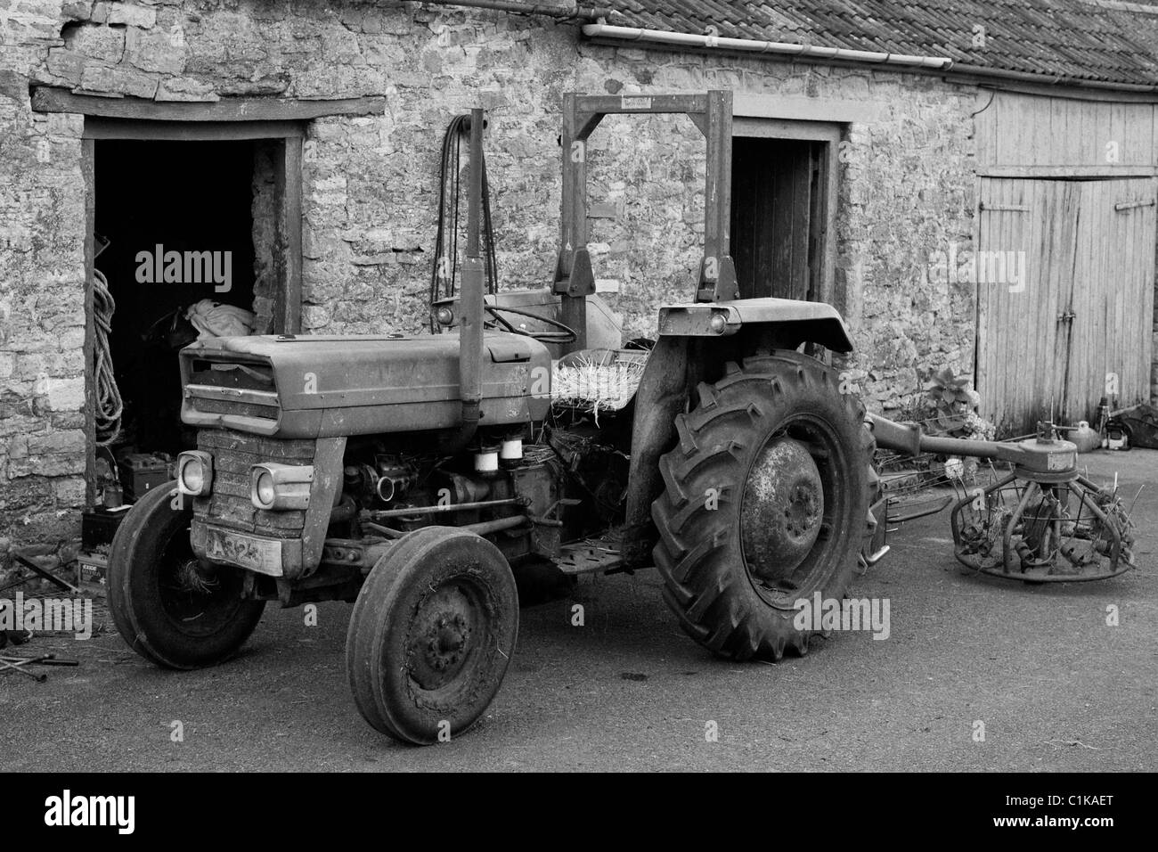 Dave Bath's old Massey Ferguson at Ubley farm complete with hay rake and straw set cushion - Stock Image
