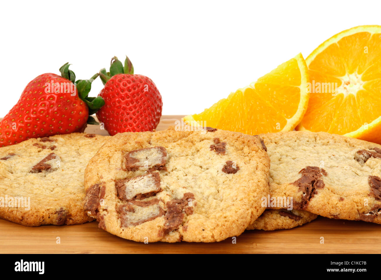 Chocolate chip cookies arranged on a wooden board and decorated with strawberries and oranges. White background - Stock Image
