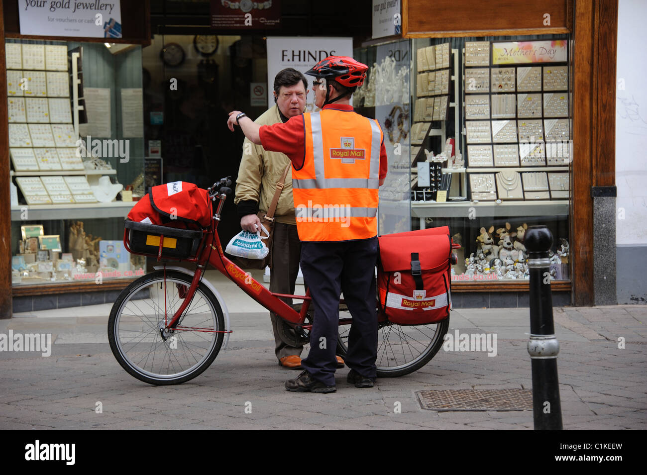 Postman with a bicycle giving directions to a passerby on his town centre round - Stock Image