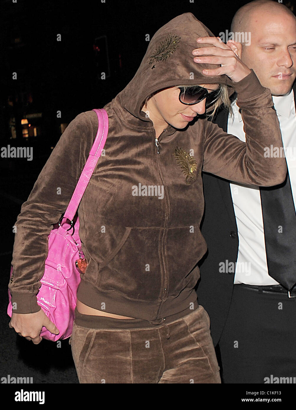 Britney Spears arrives at a hotel wearing a brown velour tracksuit, flanked by her minders. Spears performed in Stock Photo