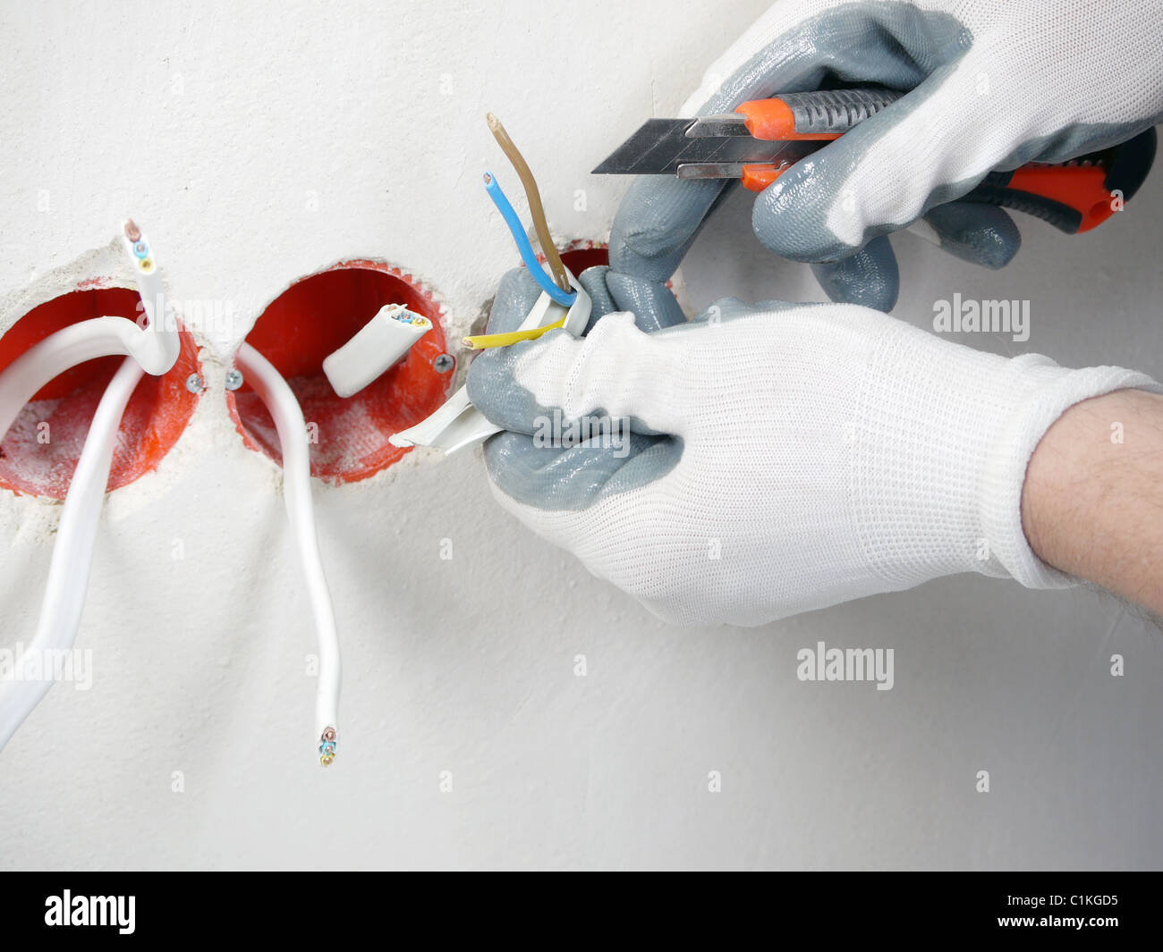 Closeup of electrician\'s hands stripping electrical wires for wall ...