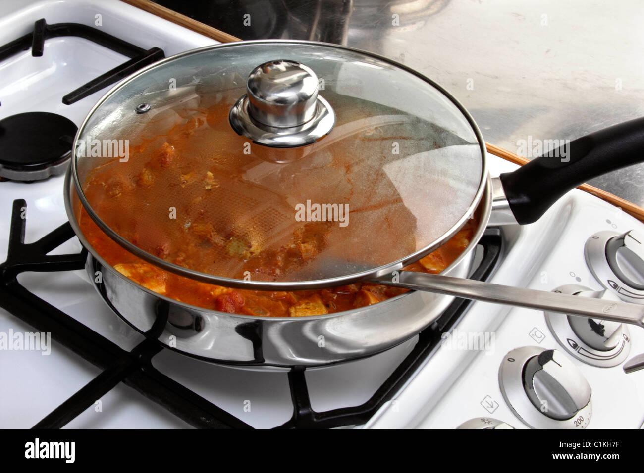 Chicken rogan josh cooking in pan - Stock Image