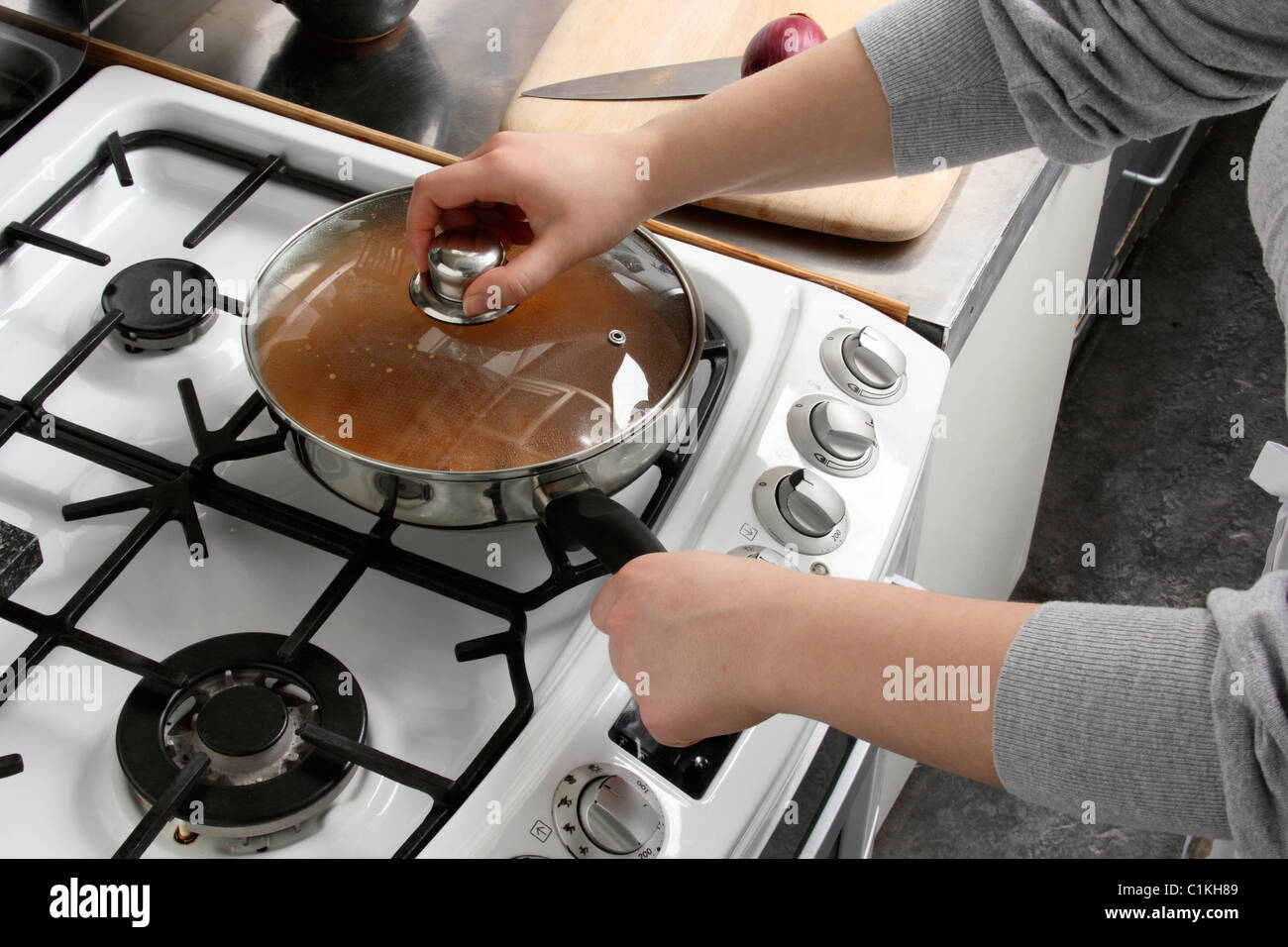 Putting a lid on a saucepan of simmering chicken rogan josh - Stock Image