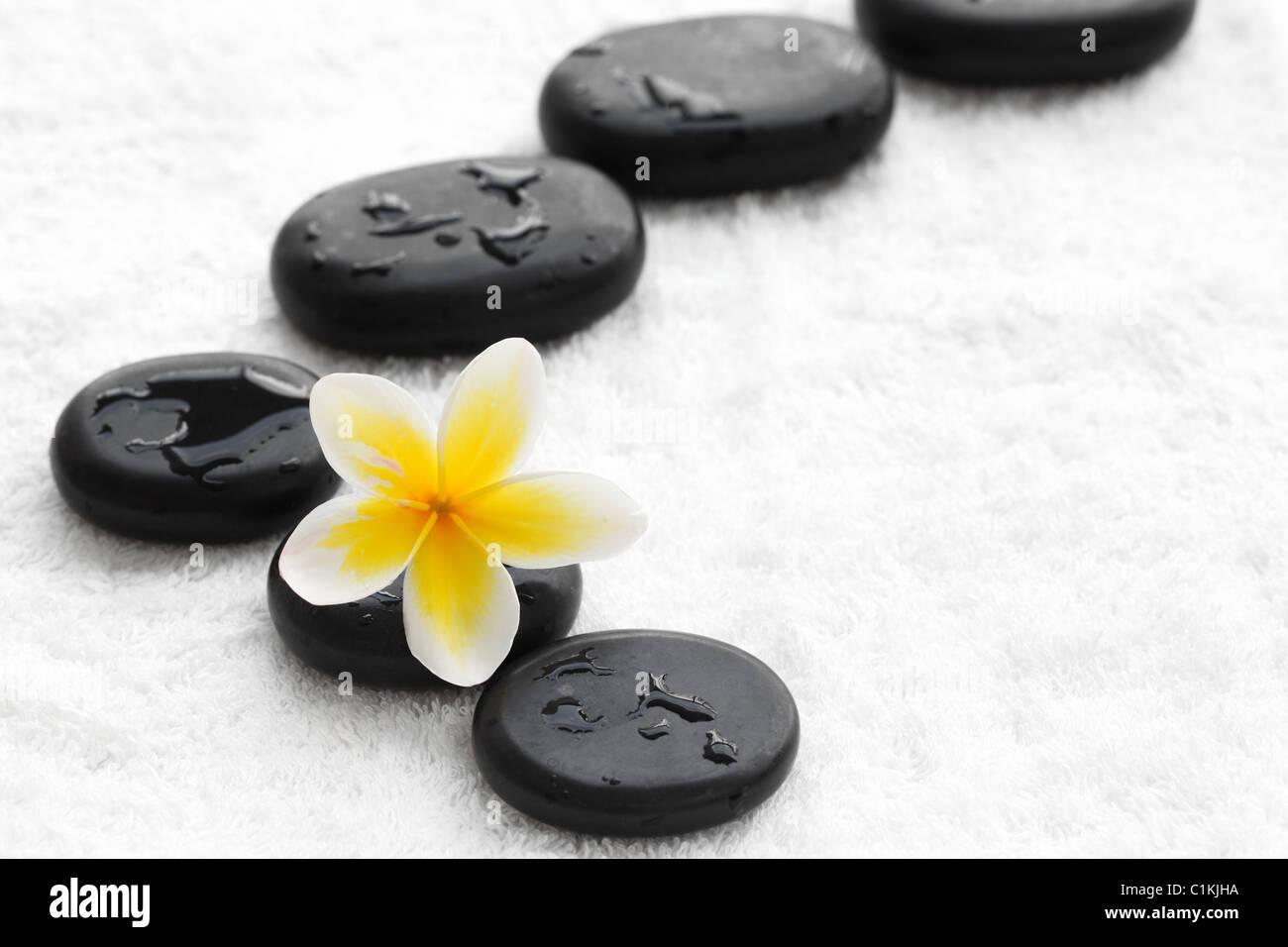 zen stones with frangipani flower on white towel - Stock Image