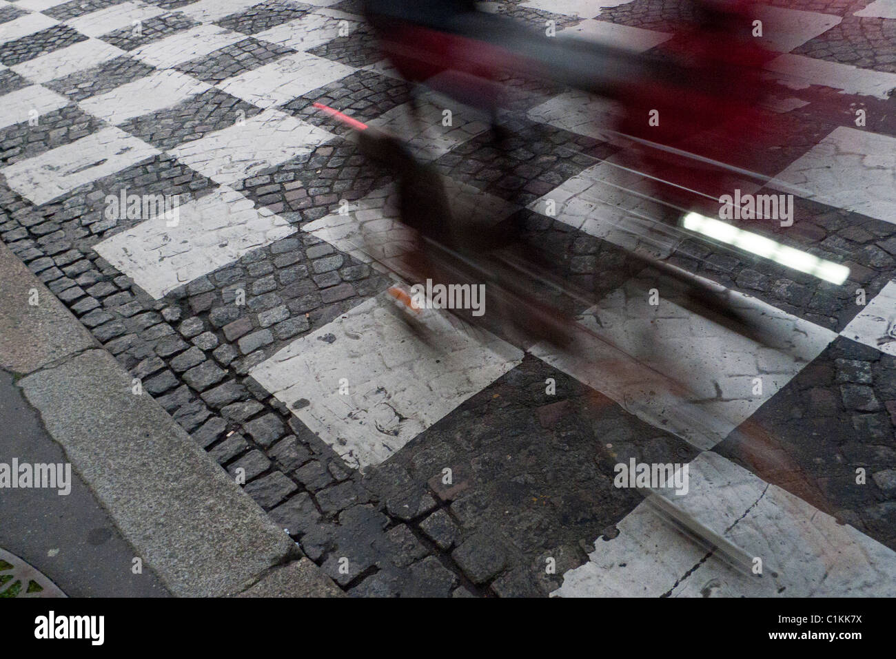 Cyclist riding over chequered road markings, Paris France - Stock Image