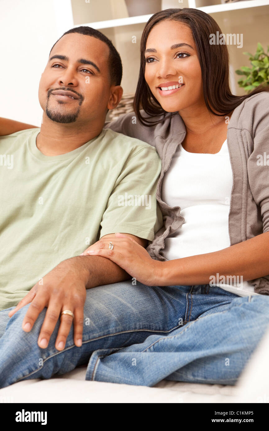 A happy African American man and woman couple in their thirties sitting at home - Stock Image