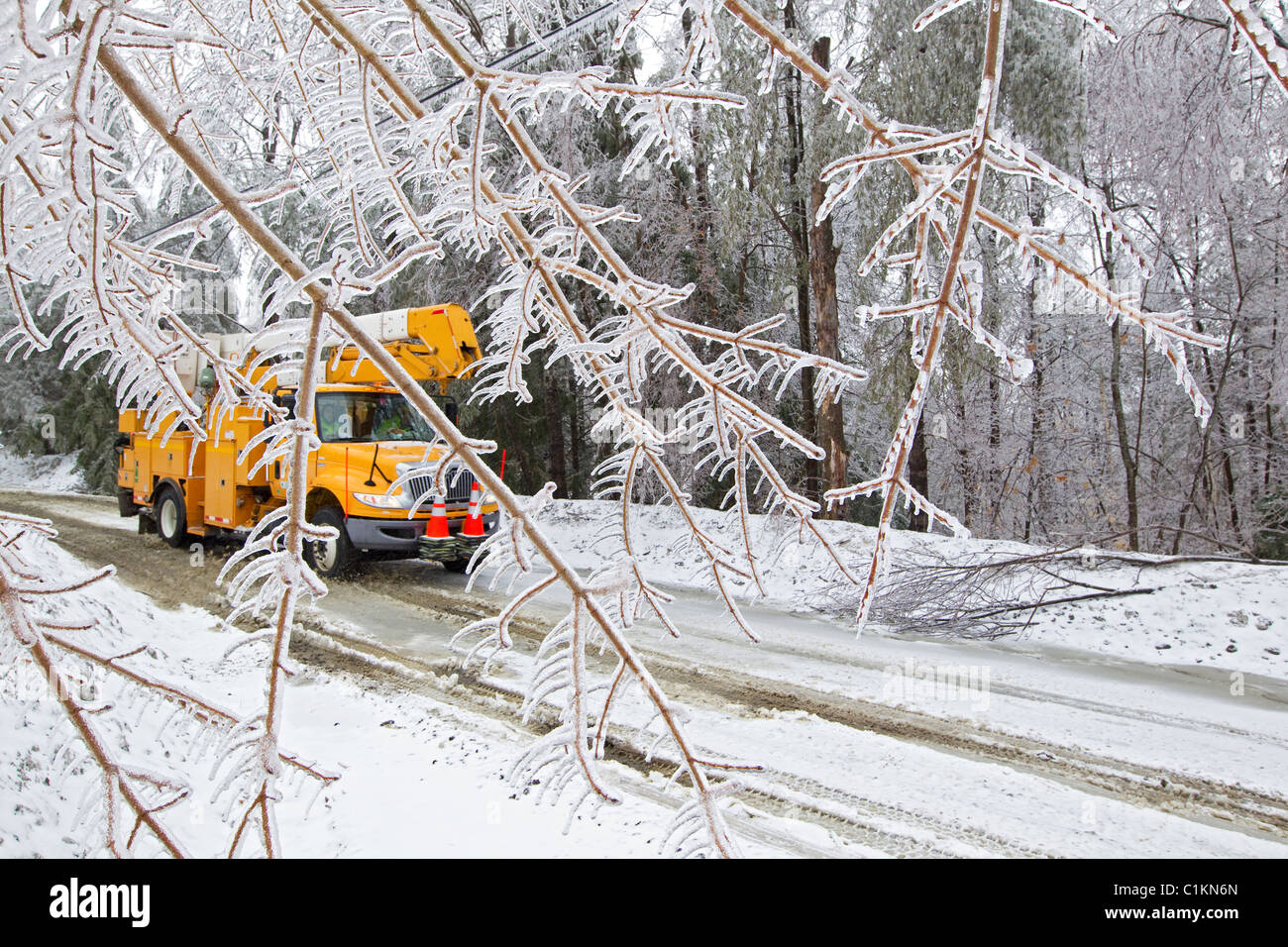 Yellow utility truck drives on snowy winter forest road after ice storm - Stock Image