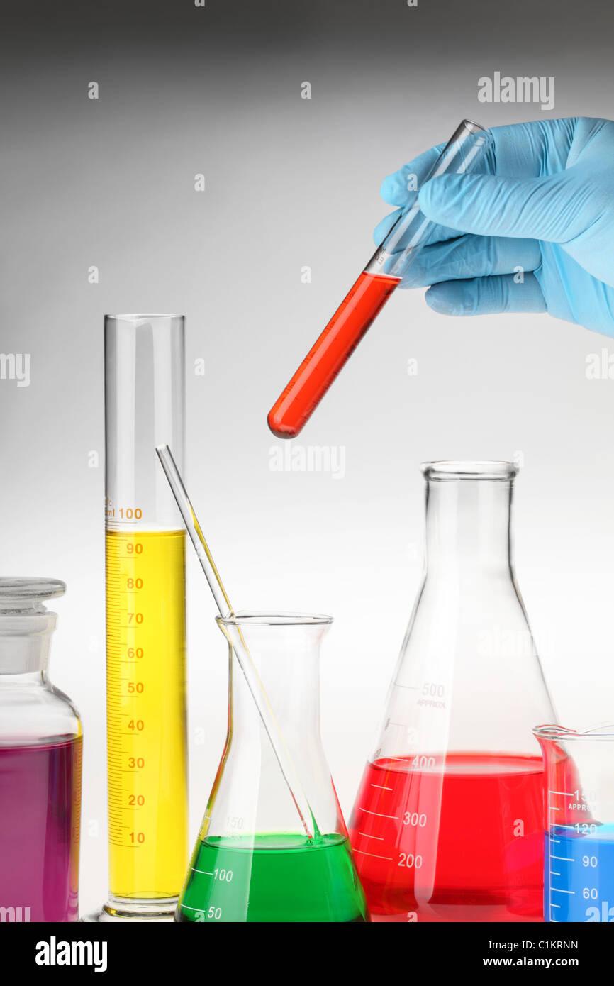 Hand holding test-tube among lab glassware - Stock Image