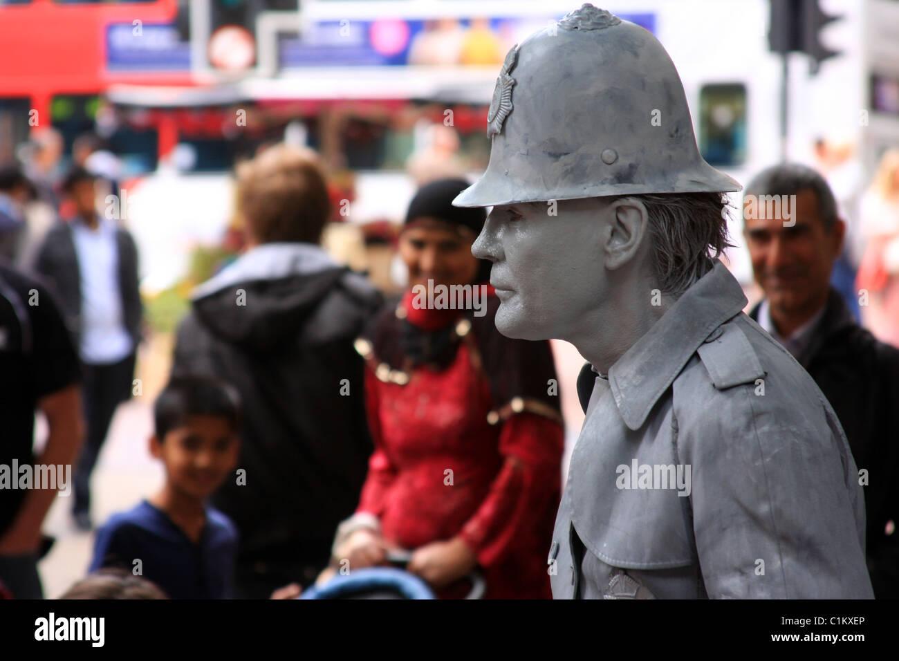Street entertainer dressed as policeman statue in Birmingham UK - Stock Image